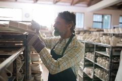 Male potter placing craft product on shelf. In pottery workshop royalty free stock image