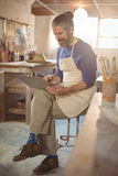 Male potter sitting on stool using laptop Stock Photo