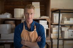 Male potter standing with arms crossed in pottery workshop. Portrait male potter standing with arms crossed in pottery workshop Royalty Free Stock Photos
