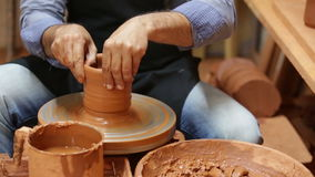 Male potter working with clay. Portrait of cheerful male potter working with clay on pottery wheel in atelier stock video footage