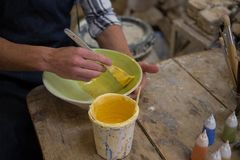Male potters hand painting a bowl in pottery workshop. Mid-secion of male potters hand painting a bowl in pottery workshop stock photos