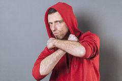 Male power concept for unhappy 40s man. Male power concept - unhappy 40s man wearing an adolescent hoodie countering fight with both arms crossed,studio shot Stock Photos