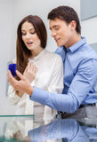 Male presents engagement ring to his woman. Male presents engagement ring to his women at jeweler's shop. Concept of wealth and luxurious life stock photography