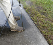 Male Pressure Washing Sidewalk. Male do-it-yourselfer pressure washing the sidewalk in front of his house Royalty Free Stock Images