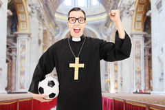 Male priest with football cheering in a church Stock Photos