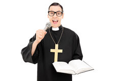 Male priest reading a prayer on microphone. Isolated on white background Royalty Free Stock Photo
