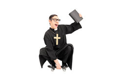 Male priest riding a small skateboard Stock Image