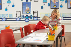 Male Primary School Pupil And Teacher Working Stock Photo