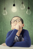 Male primary school student sitting under light bulb Stock Image