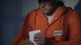 Male prisoner in handcuffs looking at photo, feeling miserable, missing beloved. Stock footage stock video footage