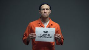 Male prisoner holding End solitary confinement sign imprisoned people rights. Stock footage stock video footage