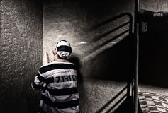 Male prisoner is sitting in the corner and praying in a small pr Stock Image