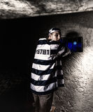 Male prisoner wearing prison uniform looked back while trying to Royalty Free Stock Image