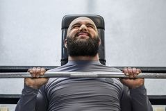 Male professional athlete pressing barbell, working hard before competition stock photos