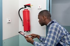 Male Professional Checking A Fire Extinguisher. Close-up Of African Male Professional Checking A Fire Extinguisher royalty free stock photo