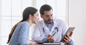 Doctor showing medical test results on digital tablet consulting patient