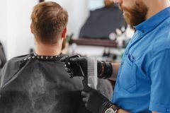 The man barber serves the client in the salon royalty free stock photos