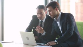 Male professional investment advisor consulting client with laptop at meeting