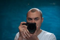 Male professional photographer posing with camera. Against blue background Royalty Free Stock Images