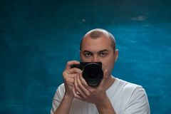 Male professional photographer posing with camera. Against blue background Stock Photo