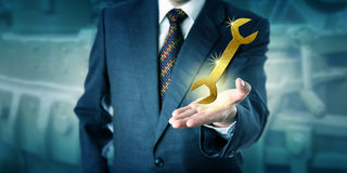 Male Professional Is Presenting A Golden Wrench Royalty Free Stock Image