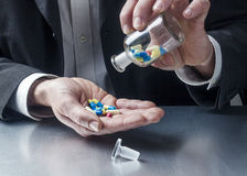 Male professional taking pills at the office Royalty Free Stock Photography