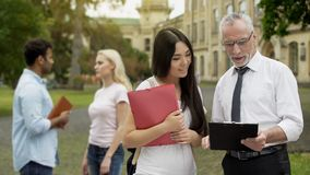 Male professor discussing thesis with asian female student near university. Stock photo stock photos