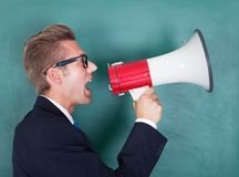 Male professor shouting though megaphone Stock Photography