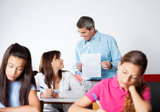 Male Professor Showing Paper To Student During Stock Photos