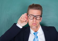 Male professor trying to hear. Male Lecturer Standing In Front Of Chalkboard And Trying To Listen Stock Photos