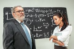 Male professor and young woman against chalkboard in classroom. Male senior professor and young female student against chalkboard in classroom. Human emotions Royalty Free Stock Photos