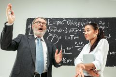 Male professor and young woman against chalkboard in classroom. Male senior professor and young female student against chalkboard in classroom. Human emotions Stock Photography