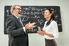 Male professor and young woman against chalkboard in classroom. Male senior professor and young female student against chalkboard in classroom. Human emotions Stock Image