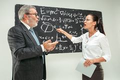 Male professor and young woman against chalkboard in classroom. Male senior professor and young female student against chalkboard in classroom. Human emotions Royalty Free Stock Image