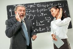 Male professor and young woman against chalkboard in classroom. Male senior professor and young female student against chalkboard in classroom. Human emotions Stock Photo