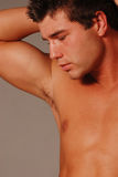Male profile. Hadsome young man on grey arm resting on head shirtless Stock Images