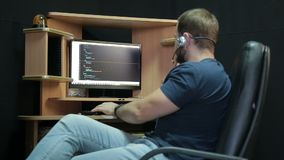 Male programmer relaxed working with code stock video footage