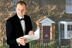 Male property agent. Cheerful male property agent handing a form and paper to viewer with beautiful property in the background Stock Photo