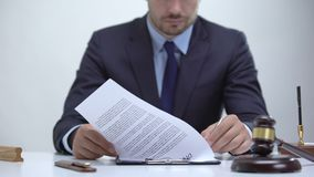 Male prosecutor reading documentary evidence, preparing case strategy for court. Stock footage stock footage