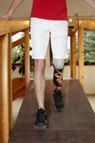 Male prosthesis wearer training to walk. Male prosthesis wearer with lower leg amputation training to walk in a special course or interior area where surfaces Royalty Free Stock Images