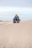 Male in protection eastern clothes pouring sand stock photos