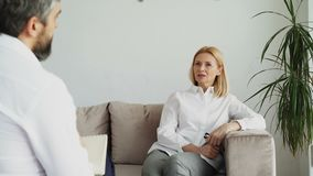 Male psychoanalyst listening adult female patient with depression in psychologist office. Indoors stock footage