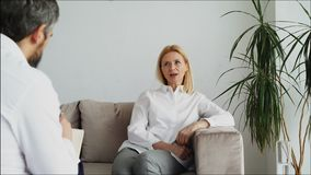 Male psychoanalyst listening adult female patient and writing notes in psychologist office. Indoors stock video