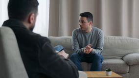 Male psychoanalyst listening patient and writing notes in psychologist office stock video