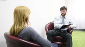 Male psychologist and his female patient during therapy. Receiving psychologist stock video footage