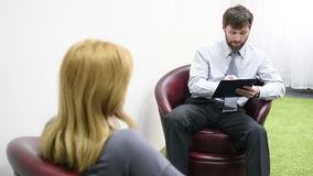Male psychologist and his female patient during therapy. Receiving psychologist stock footage