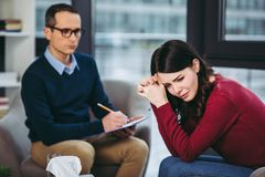 Male psychologist listening to patient. Male psychologist listening to female patient and making notes in document on clipboard Stock Photo