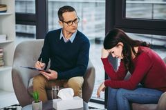 Male psychologist listening to patient. Male psychologist listening to female patient and making notes in document on clipboard Stock Image