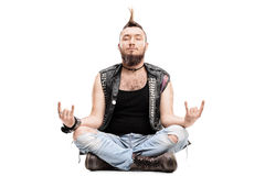 Male punk meditating seated on the floor. And making a rock gesture with his hands isolated on white background Royalty Free Stock Photos