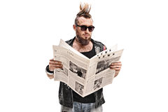 Male punk rocker reading a newspaper Royalty Free Stock Image
